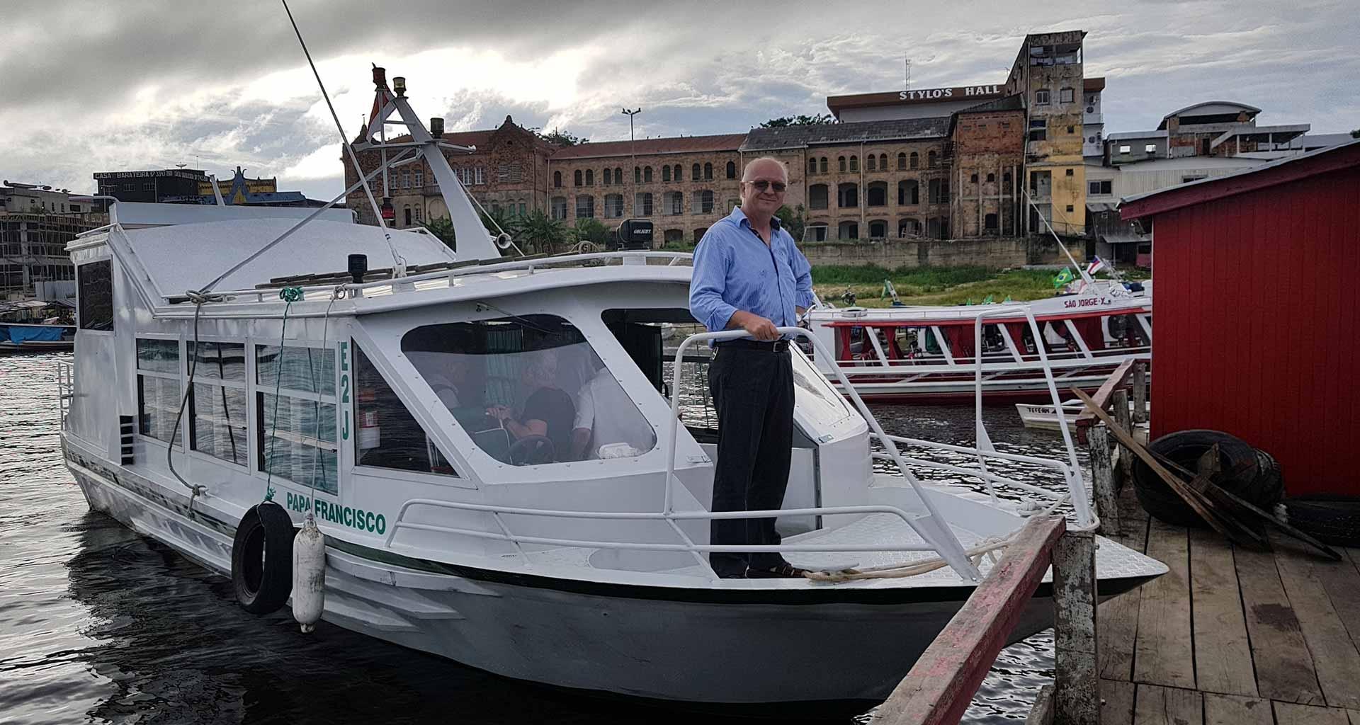 Pe. Pedro no barco Papa Francisco, doado pela ACN, em frente ao Seminário de Tefé, também apoiado pela Obra em resposta ao apelo do Papa.