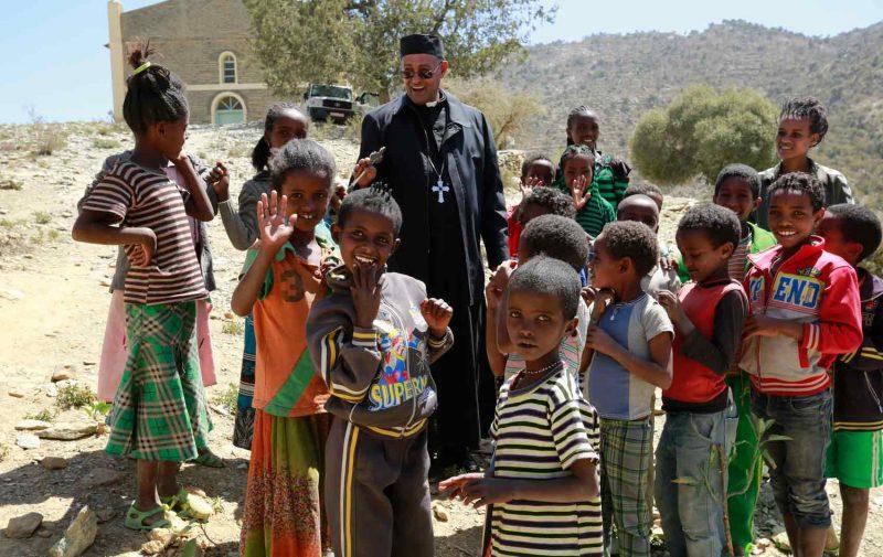 Bispo e crianças em igreja na fronteira da Etiópia