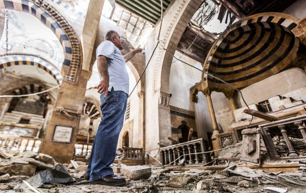 Homem aponta a destruição em meio às ruínas da catedral católica armênia severamente danificada durante a guerra