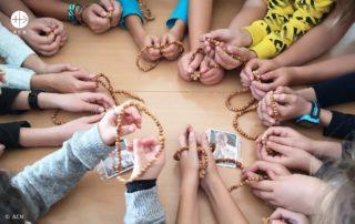 Foto de criançs rezando o terço